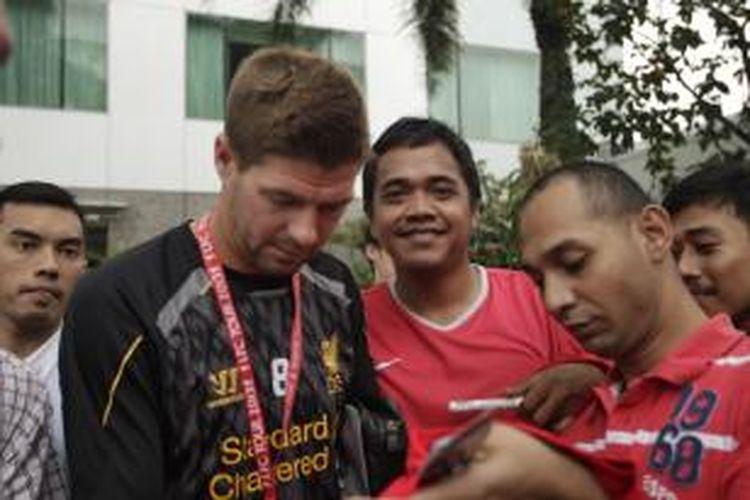 Pemain dan juga kapten tim Liverpool Steven Gerrard memberikan tanda tangan kepada fans seusai bersantai di Pool Site Hotel Mulia, Senayan, Jakarta, Kamis (18/7/2013). Liverpool akan bertanding melawan Timnas Indonesia di Stadion Utama Gelora Bung Karno, pada Sabtu 20 Juli 2013.
