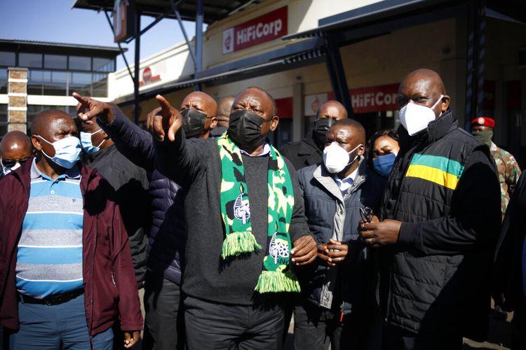 Presiden Afrika Selatan Cyril Ramaphosa, (tengah) bersyal hijau dalam kunjungan ke Soweto, Afrika Selatan, Minggu 18 Juli 2021.