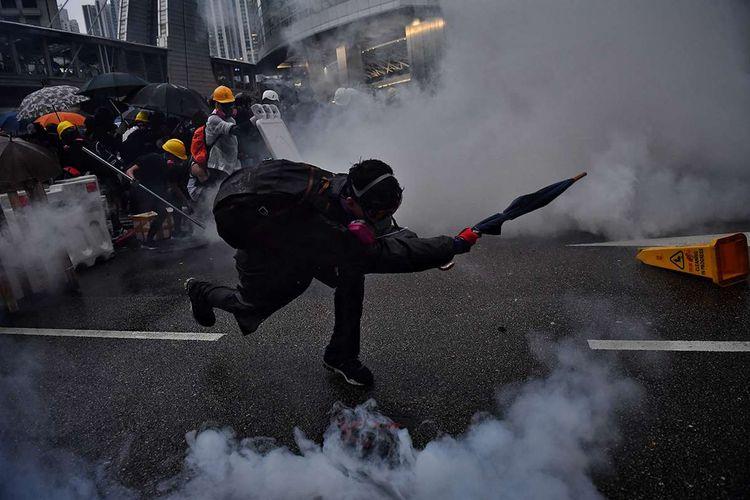 Pengunjuk rasa pro-demokrasi berusaha mengembalikan gas air mata ke arah polisi, saat terjadi bentrokan di Tseun Wan, Hong Kong, Minggu (25/8/2019). Aksi protes telah bergulir selama 3 bulan terakhir di Hong Kong, dimulai ketika Kepala Eksekutif Hong Kong Carrie Lam memperkenalkan undang-undang yang bisa mengekstradisi kriminal ke China daratan.