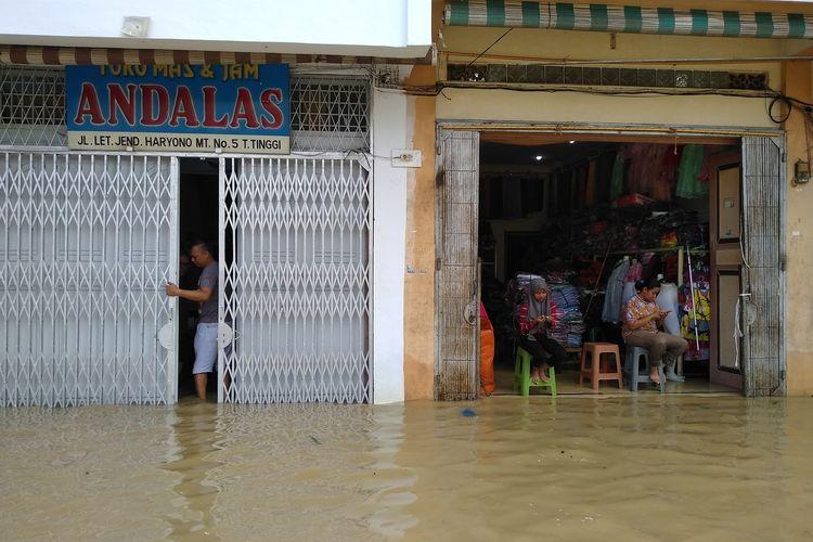 Seorang pria menutup pintu tokonya di Jalan Jend. MT Haryono, Tebing Tinggi, Senin (16/12/2019). Daerah pertokoan ini kebanjiran karena meluapnya Sungai Bahilang sejak dini hari.