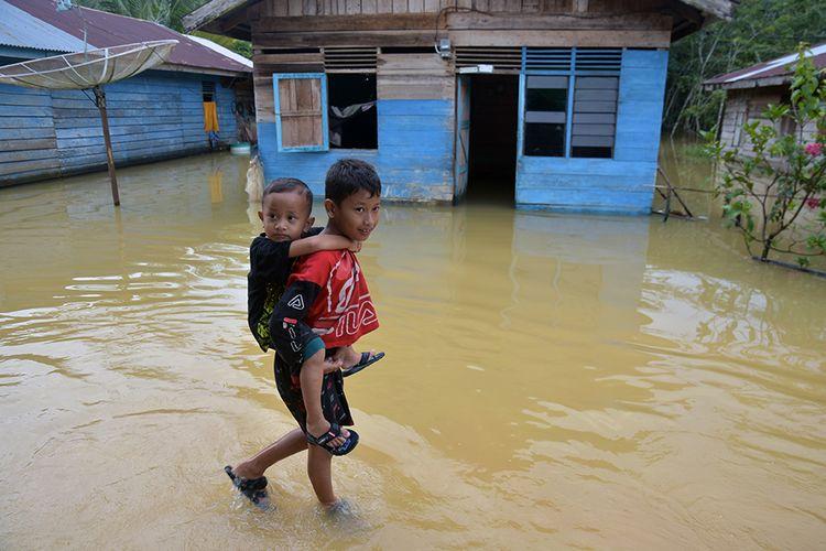 Seorang bocah menggendong kawannya yang lebih muda saat melintasi banjir akibat luapan Sungai Subayang di Kecamatan Gunung Sahilan Kabupaten Kampar, Riau, Rabu (11/12/2019). Berdasarkan data Badan Penanggulangan Bencana Daerah (BPBD) Kampar, tingginya intensitas hujan mengakibatkan air sungai meluap sehingga membanjiri dua desa di Kecamatan Gunung Sahilan, akses jalan desa terputus dan sekitar 276 kepala keluarga terdampak banjir.