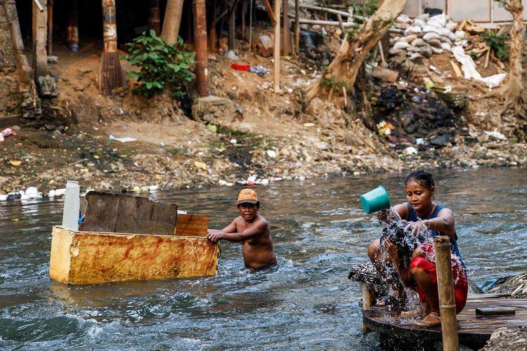 Warga beraktivitas di pemukiman padat penduduk di bantaran Sungai Ciliwung, Manggarai, Jakarta, Minggu (28/7/2019).