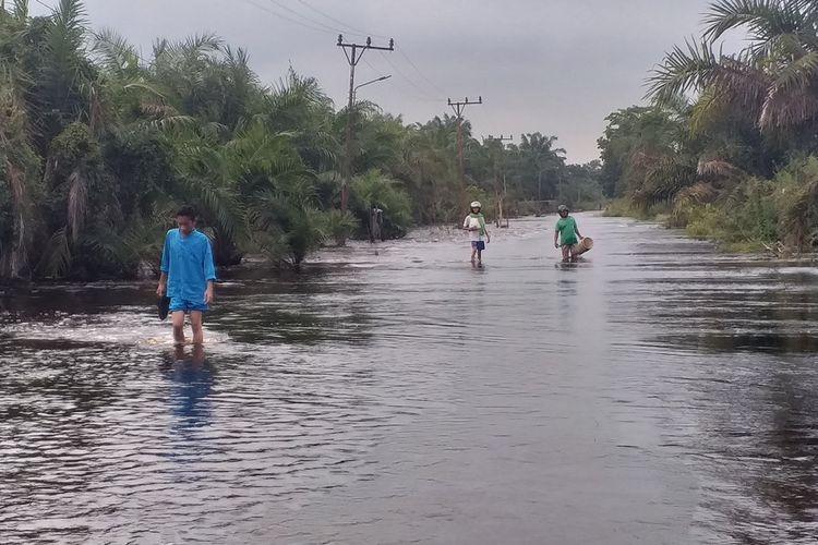 Muhammad Mursal Hafis (17) melewati arus banjir yang merendam akses jalan untuk pergi ke sekolah di Desa Buluh Cina, Kecamatan Siak Hulu, Kabupaten Kampar, Riau, Jumat (20/12/2019) pagi.