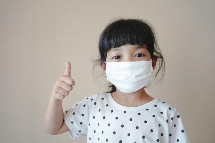 Ilustrasi anak memakai masker.