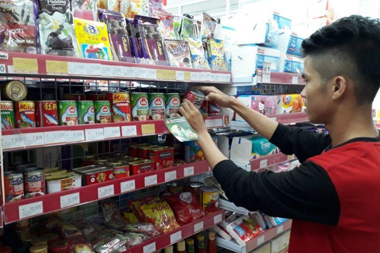 Salah seorang warga terlihat serius melakukan pengecekan salah satu sarden kaleng. Saat ini BPOM telang mengumumkan ada 27 merek sarden kaleng mengandung cacing.