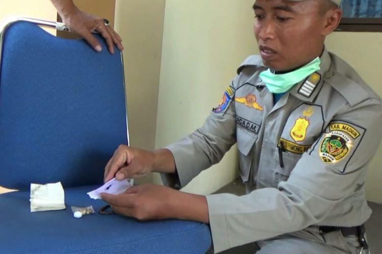 Anggota Satpol PP  menemukan jimat milik peserta tes cpns Kabupaten Madiun berupa rambut yang dibungkus dalam kertas.