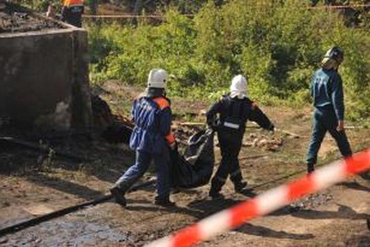 Petugas pemadam kebakaran membawa kantung jenazah salah seorang korban kebakaran di sebuah rumah sakit jiwa di desa Luka, Provinsi Novgorod, Rusia, Jumat (13/8/2013).