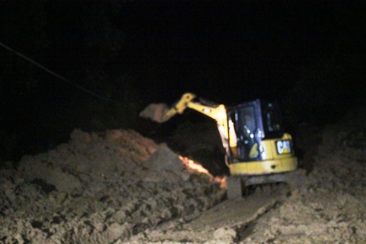 Alat berat berupaya menyingkirkan material longsor yang menutup badan jalan lintas selatan Cianjur, Jawa Barat, Kamis (19/3/2020) malam.