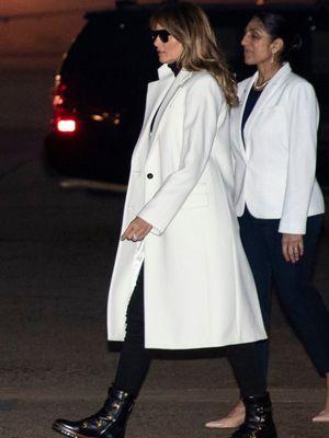 Melania menggenakan mante putih panjang yang dilapisi turtleneck dan celana jeans hitam. Pada kakinya, perempuan Slovenia itu mengenakan sepasang sepatu bot kreasi Dior.