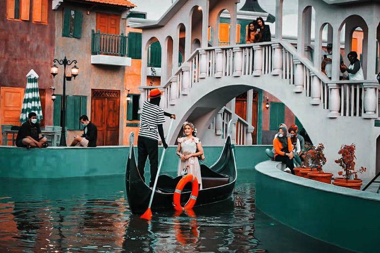 Pemandangan pengunjung naik perahu di atas sungai berlatar Kota Venesia, Italia. Bukan di Venesia asli, foto ini diambil di Dusun Semilir Eco Park, Kecamatan Bawen, Kabupaten Semarang, Jawa Tengah.