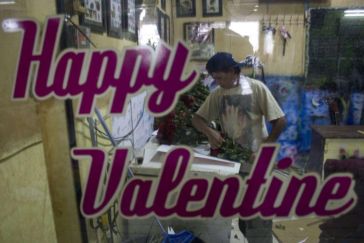 Penjual menyelesaikan pengemasan bunga mawar merah asal Malang di kawasan Pasar Bunga Rawa Belong, Sukabumi Utara, Kebon Jeruk, Jakarta Barat, Senin (10/2/2020). Menjelang valentine, harga bunga mawar merah di Pasar Rawa Belong naik.
