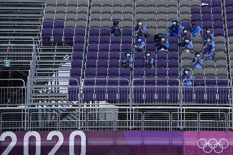 Sejumlah relawan beristirahat sambil memberikan dukungan saat pertandingan panahan Olimpiade Tokyo 2020 di Yumenoshima Park Archery Field, Tokyo, Jepang, Senin (26/7/2021). Penyelenggaraan Olimpiade yang diselenggarakan tanpa penonton dari kalangan umum tersebut merupakan keputusan di tengah kondisi darurat Covid-19 yang sedang diberlakukan di Ibu Kota Jepang.