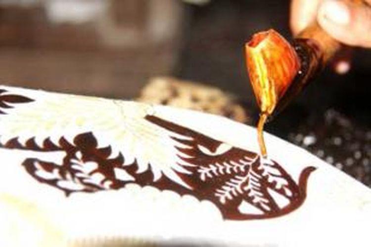 Seorang perajin batik, Sabtu (7/12/2013), tengah melakukan proses menembok atau menutup pola yang bakal dibiarkan putih dengan menggunakan malam (lilin). Proses itu dilakukan pada selembar kain batik di Sanggar Batik Katura, Desa Trusmi, Kecamatan Plered, Kabupaten Cirebon, Jawa Barat.