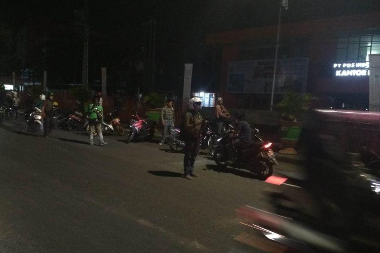Pemandangan warga yang terpaksa menghentikan perjalanan di sekitar lokasi bentrokan antara aparat kepolisian dengan massa aksi di Jalan A. P. Pettarani, Makassar, Sabtu (28/9/2019) dini hari.