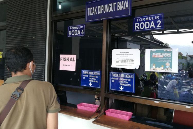 seorang wajib pajak menunggu berkas di depan loket fiskal di kantor Samsat Kota Solo