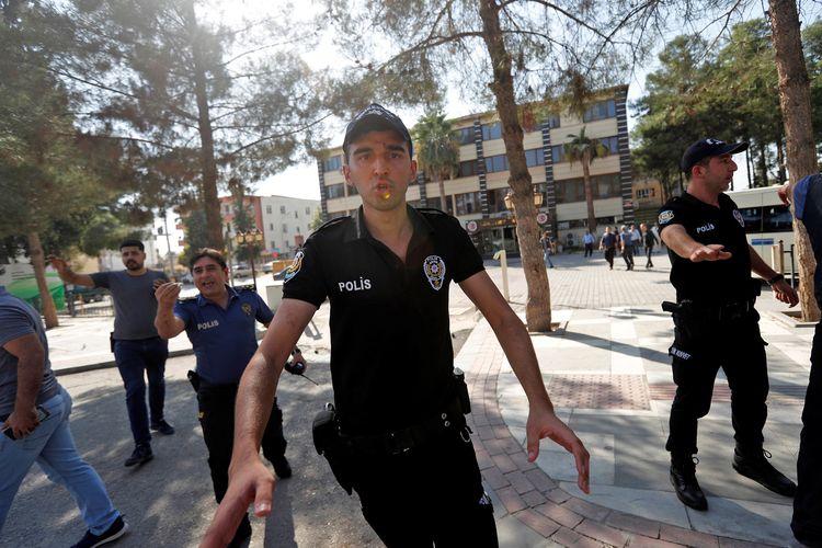 Polisi mencoba mencegah warga untuk tidak mendekati Gedung Pemerintahan Akcakale, Turki, setelah mortar dari Suriah menghantam bangunan tersebut pada 10 Oktober.