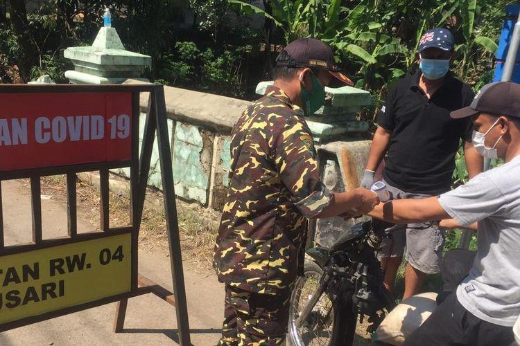Warga yang akan memasuki RW 4 Desa Randusari, Kecamatan Pagerbarang, Kabupaten Tegal, Jawa Tengah diperiksa saat wilayah itu dilockdown menyusul puluhan warga positif Covid-19, Selasa (8/6/2021).