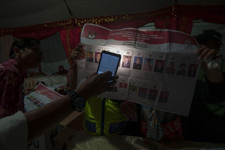 Anggota KPPS memastikan titik pencoblosan surat suara pada penghitungan hasil pemilihan Calon Legislator Dewan Perwakilan Daerah (DPD) di TPS 05 Kelurahan Lolu Utara, Palu, Sulawesi Tengah, Rabu (17/4/2019). Penghitungan surat suara untuk Pileg di TPS tersebut masih terus berlangsung hingga malam hari.