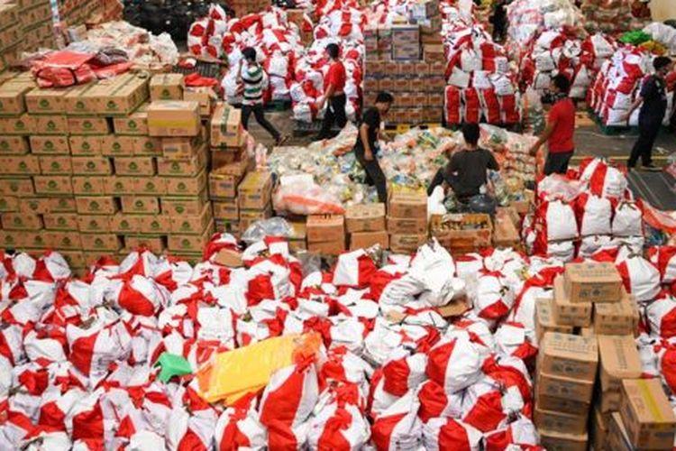 Pekerja mengemas paket bantuan sosial (bansos) di Gudang Food Station Cipinang, Jakarta, Rabu (22/04).