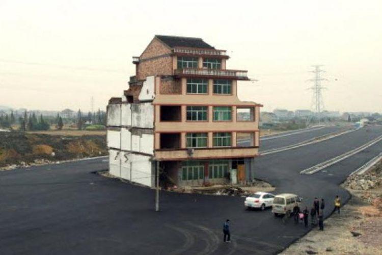 Sebuah rumah berdiri di tengah jalan raya bebas hambatan di kawasan Wenling, China. Sang pemilik menolak semua tawaran ganti rugi pihak kontraktor yang hendak membangun jalan. Alhasil, rumah itu pun berdiri di tengah jalan.