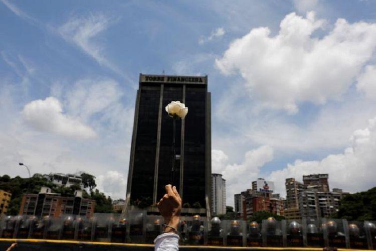 Seorang demonstran mengacungkan bunga mawar di depan polisi antihuru-hara dalam unjuk rasa perempuan di Venezuela untuk menentang pemerintahan Presiden Nicolas Maduro di Caracas, Sabtu (6/5 2017).