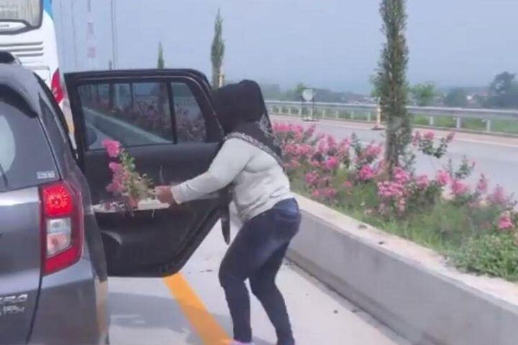 Tangkap layar dari video yang viral yang menampilkan seorang perempuan penumpang mobil mencuri bunga di Tol Pandaan-Malang.