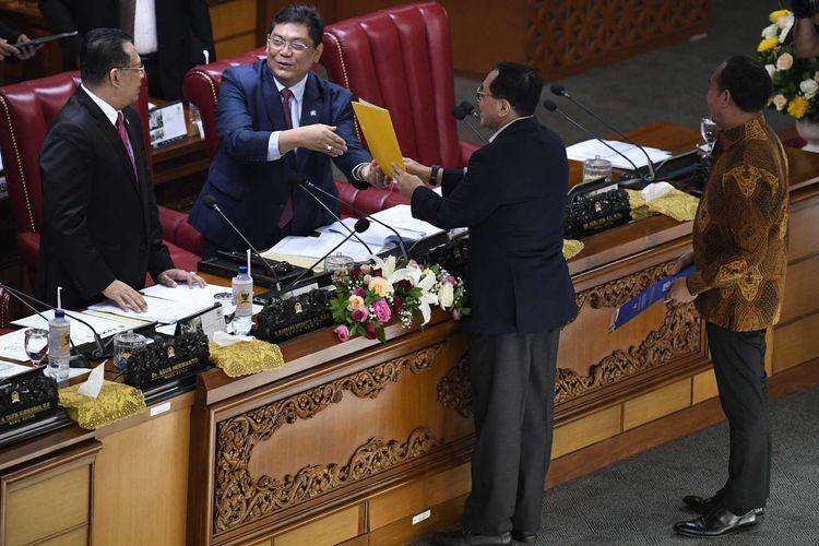 Pimpinan Dewan Perwakilan Rakyat (DPR), Utut Adiyanto (kedua kiri) dan Bambang Soesatyo (kiri) menerima tanggapan tertulis dari fraksi-fraksi DPR saat Rapat Paripurna Masa Persidangan I Tahun Sidang 2019-2020 di Kompleks Parlemen Senayan, Jakarta, Kamis (5/9/2019). Rapat paripurna tersebut membahas RUU tentang Perubahan Atas UU Nomor 2 Tahun 2018 tentang perubahan kedua atas Undang-Undang No.17 Tahun 2014 tentang MPR, DPR dan DPRD (UU MD3), serta RUU tentang Perubahan Atas UU Komisi Pemberantasan Tindak Pidana Korupsi (KPK).