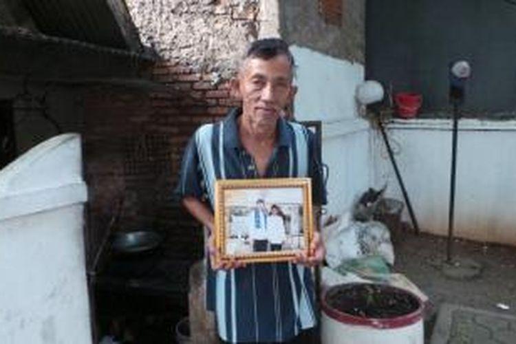 Juru kunci atau penjaga makam Pangerang Wijaya Kusuma, Hadi Doyo (63), memegang fotonya bersama Wakil Gubernur DKI Jakarta Basuki Tjahaja Purnama. Hadi kini dapat menikmati hasil kerja kerasnya dengan mendapatkan gaji sesuai upah minimum provinsi, yaitu Rp 2,2 juta per bulan.