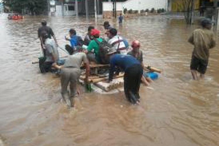 Warga menggunakan berbagai alternatif untuk menembus banjir di kawasan Kampung Melayu, Jakarta Timur, Senin (13/1/2014).