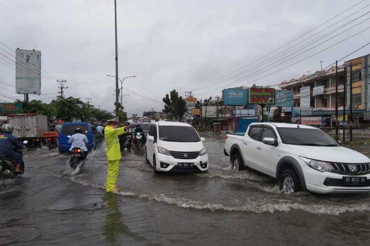 Petugas kepolisian lalu lintas Polsek Tampan mengurai kemacetan yang terjadi di Jalan HR Soebrantas Kota Pekanbaru yang tergenang akibat banjir pada Selasa (4/8/2020) pagi. Dok Polsek Tampan