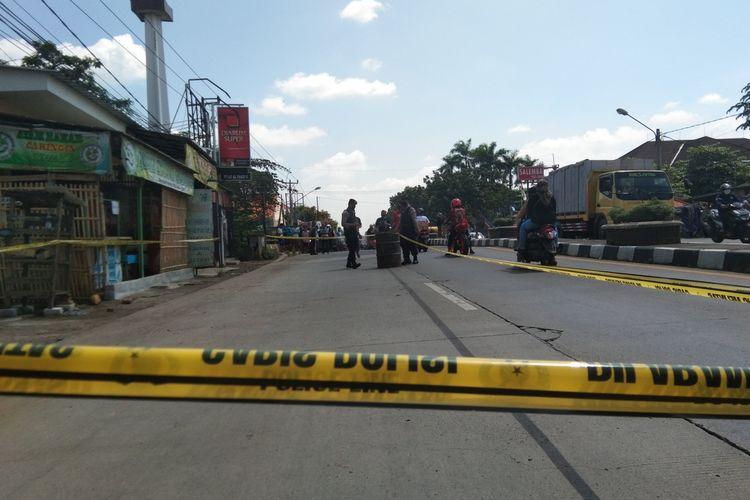 Petugas tengah memasang garis polisi di lokasi penemuan benda diduga bom di Jalan Ahmad Yani Cikampek, Desa Cikampek Selatan, Kecamatan Cikampek, Karawang, Selasa (2/6/2020).