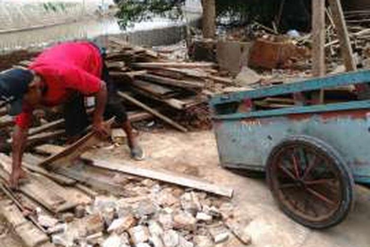 Rumawi sedang memungut sisa kayu bekas gusuran di Bukit Duri, Jakarta Selatan. Selasa (4/10/2016)