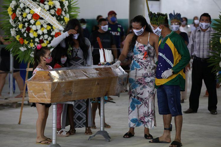 Prosesi pemakaman kepala suku Kokama yang meninggal karena Covid-19. Peti matinya terbuat dari kayu dan dibungkus plastik. Pemakaman Messias Kokama (53) diiringi dengan tarian dan nyanyian oleh masyarakat setempat di Manaus, Brasil, 14 Mei 2020.