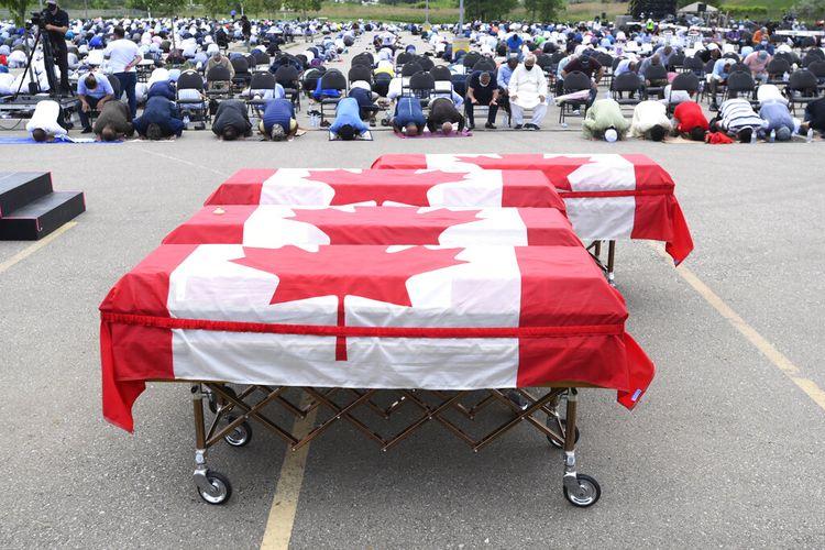 Para pelayat berdoa saat peti mati terbungkus bendera Kanada berbaris di pemakaman untuk empat anggota keluarga Muslim yang tewas dalam serangan kendaraan mematikan, di Islamic Center of Southwest Ontario di London, Ontario, pada Sabtu, 12 Juni 2021.