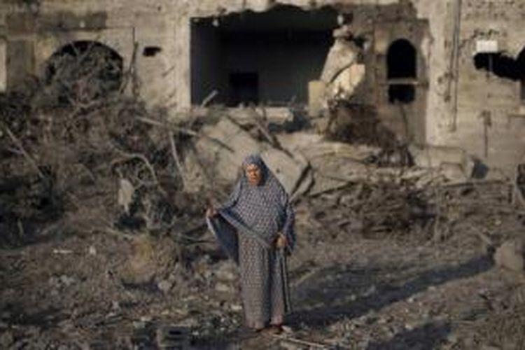 Seorang wanita Palestina berdiri di tengah puing-puing gedung yang hancur akibat serangan udara Israel ke kota Gaza, 8 Juli 2014. Puluhan warga Palestina termasuk wanita dan anak-anak turut menjadi korban dalam serangan tersebut.