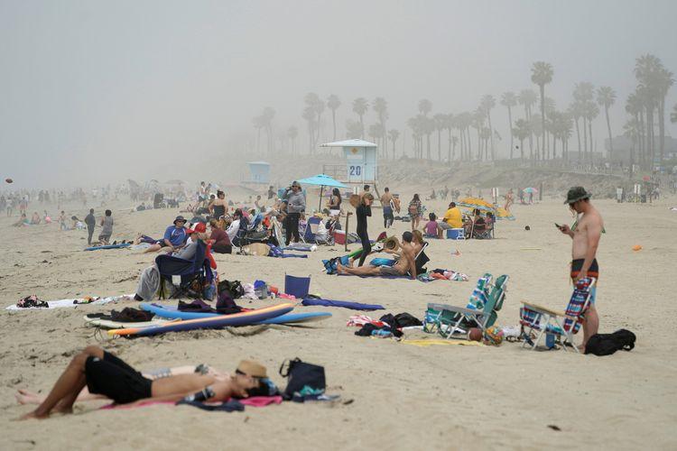 Orang-orang berjemur di Pantai Huntington, California, di tengah pandemi Covid-19 yang masih melanda dunia. Foto diambil pada Sabtu (25/4/2020).