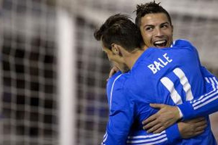 Gelandang Real Madrid, Cristiano Ronaldo (kanan), berpelukan dengan Gareth Bale, usai mencetak gol ke gawang Rayo Vallecano di ajang La Liga, Sabtu (2/11/2013). Madrid menang 3-2, dan Ronaldo menyumbang dua gol.