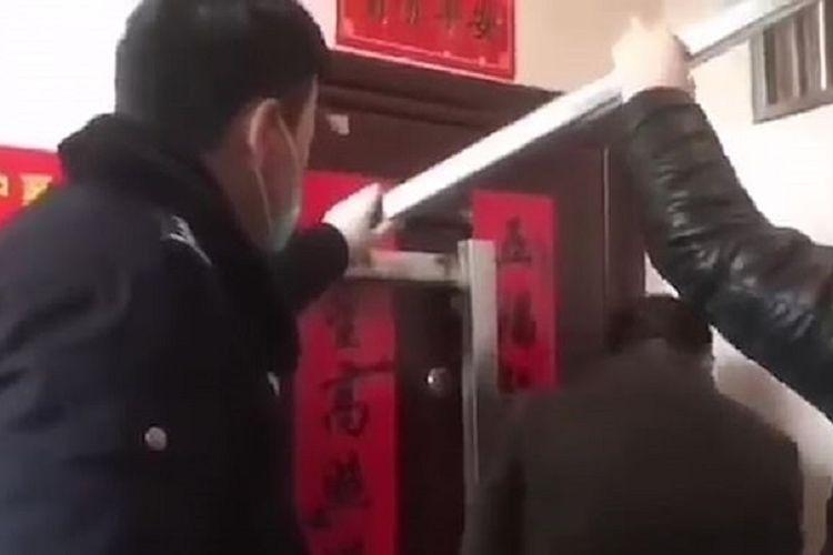 Potongan rekaman video memperlihatkan polisi memblokade rumah sebuah keluarga di Jiangsu, China, karena mereka baru saja bepergian ke Wuhan, kota asal wabah virus corona.