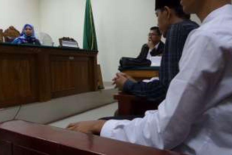 Remaja terdakwa kasus pembunuhan karyawati EF (19), RA (16, kemeja putih), mendengarkan sidang putusan mengadili dirinya dengan ditemani ayahnya, Nayudin, di Pengadilan Negeri Tangerang, Kamis (16/6/2016) pagi. Selama mendengar bacaan putusan dari majelis hakim, RA dan Nayudin saling berpegangan tangan.