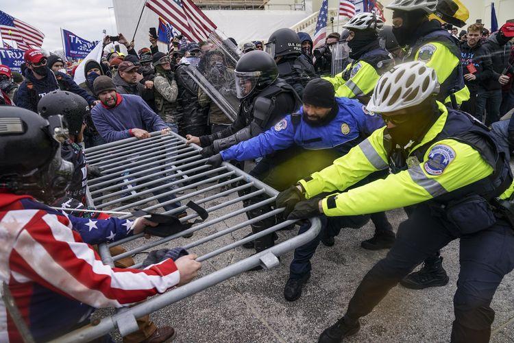 Foto tertanggal 6 Januari 2021 memperlihatkan massa pro-Donald Trump coba menjebol barikade polisi di Gedung Capitol, Washington DC.