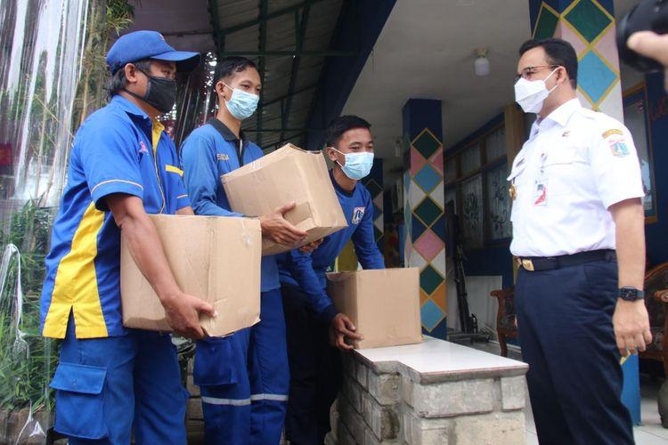 Gubernur DKI Jakarta Anies Baswedan memberikan bingkisan dan surat ucapan apresiasi kepada para petugas lapangan pengelola aliran air di DKI Jakarta.