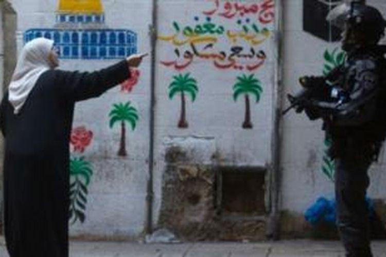 Seorang perempuan Palestina mengkonfrontasi seorang prajurit Israel yang menjaga kompleks masjil Al-Aqsa, Jerusalem yang sempat ditutup.