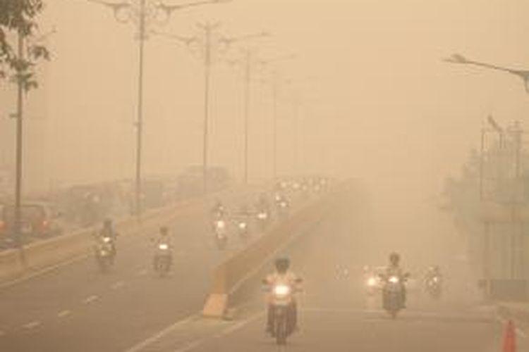 Kendaraan melintas di Jalan Jenderal Sudirman, Pekanbaru, yang diselimuti kabut asap, Kamis (13/3/2014). Kabut asap yang disebabkan kebakaran lahan dan hutan tersebut semakin pekat. Pemerintah Provinsi Riau mengimbau warga untuk menggunakan masker terkait kualitas udara yang memburuk.