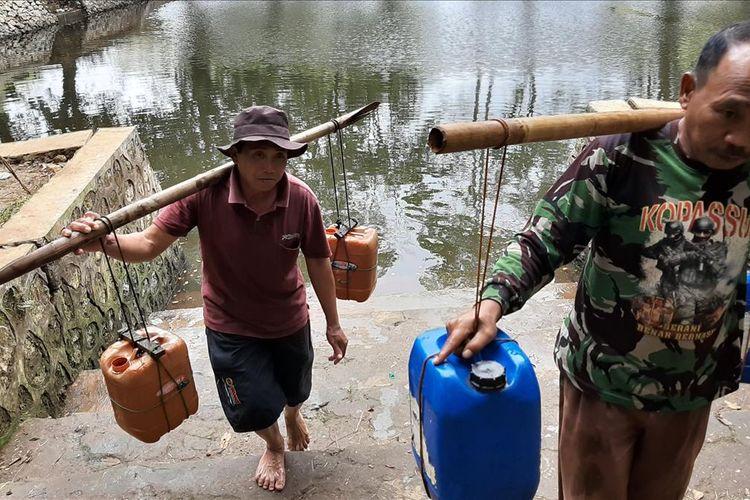 Sunaman (47) (depan) Membantu Warga Mengambil Air di Telaga Karang Kidul, Karangawen, Kecamatan Girisubo Kamis (4/7/2019)