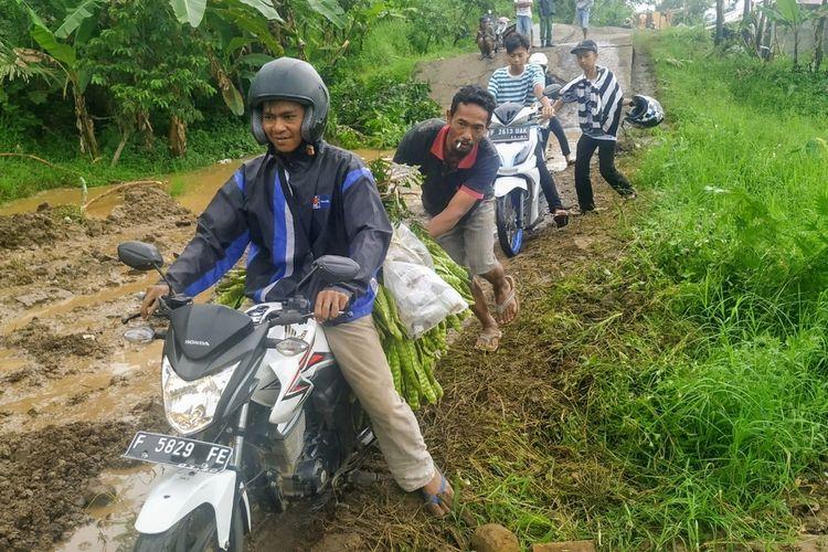Pengendara motor dibamtu warga melintaa di jalan rusak akibat tanah bergerak di Jalan Sukabumi-Sagaranten, Kampung Gunungbatu, Desa Kertaangsana, Nyalindung, Sukabumi, Jawa Barat, Senin (17/2/2020).