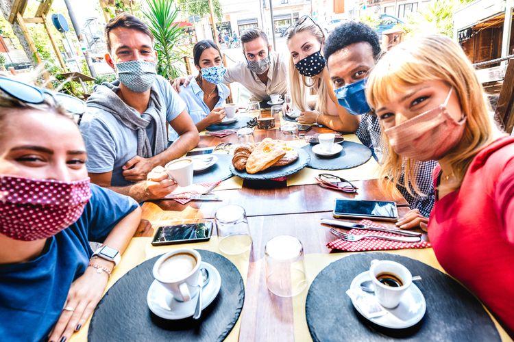 Ilustrasi sekumpulan orang selfie di restoran.