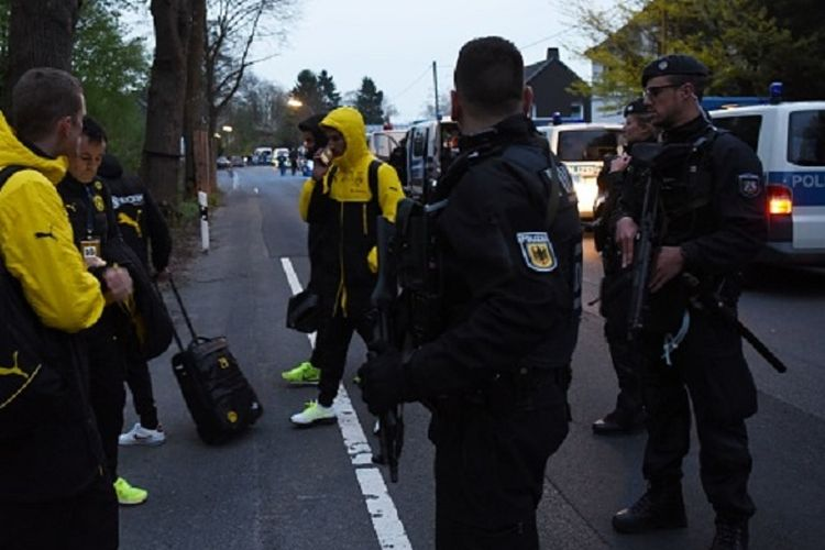 Pihak kepolisian mengevakuasi para pemain Borussia Dortmund seusai terjadi ledakan yang memecahkan salah satu kaca bus tim jelang pertandingan perempat final Liga Champions kontra AS Monaco, Selasa (11/4/2017).