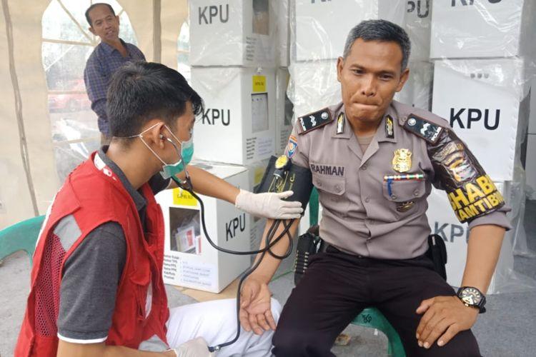Seorang relawan kesehatan PMI Kota Pontianak, Kalimantan Barat, memeriksa kesehatan petugas kepolisian yang berjaga di Kantor Camat Pontianak Barat, Senin (22/4/2019).