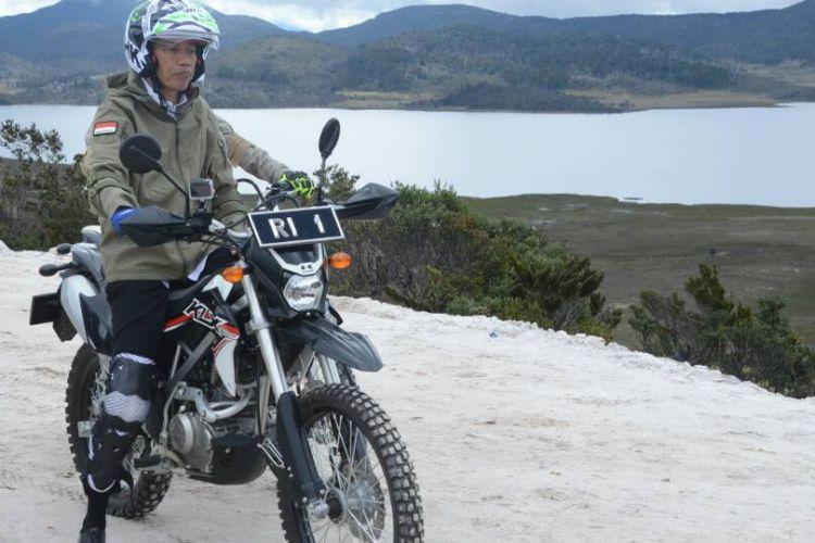 Presiden Joko Widodo menaiki motor trail untuk menjajal salah satu ruas Trans Papua yang masih dalam tahap pengerjaan, Rabu (10/5/2017).