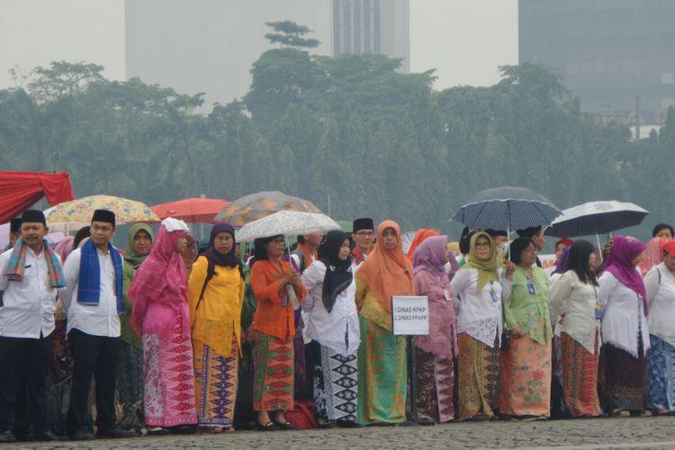 PNS DKI Jakarta mengikuti upacara peringatan HUT ke-490 DKI Jakarta di bawah rintik hujan, Lapangan Silang Monas, Kamis (22/6/2017).